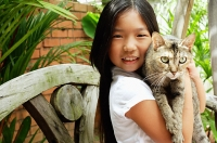 Girl holding cat, looking at camera, smiling - Asia Images Group