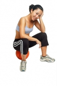 Woman sitting on basketball, looking at camera, smiling - Asia Images Group