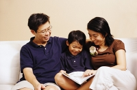 Family with one son, sitting on sofa, looking at book - Asia Images Group