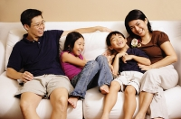 Family of four on sofa, laughing - Asia Images Group