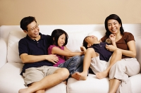 Family of four on sofa, sister tickling brother - Asia Images Group