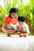 Mother and son crouching, son holding terrapin - Asia Images Group