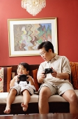 Father and son sitting side by side on sofa, playing video game - Asia Images Group