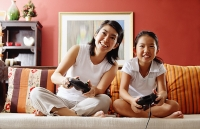 Mother and daughter in living room, playing video game - Asia Images Group
