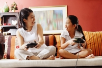 Mother and daughter on sofa, holding video game controllers, looking at each other - Asia Images Group