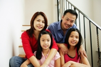 Family of four sitting on stairs, looking at camera, family portrait - Asia Images Group