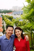 Couple standing on balcony, smiling at camera, portrait - Asia Images Group