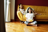 Two girls sitting in living room, one holding remote control, the other holding bowl of popcorn - Asia Images Group