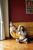 Two girls sitting in living room, one holding remote control, the other eating popcorn - Asia Images Group
