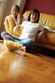Two sisters sitting in living room, looking at camera - Asia Images Group