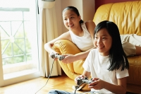 Two sisters in living room, playing video games - Asia Images Group
