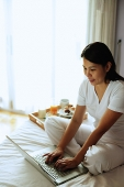 Woman sitting on bed, using laptop - Asia Images Group