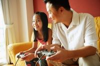 Father and daughter sitting side by side playing video games - Asia Images Group