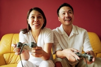 Couple playing video game - Asia Images Group