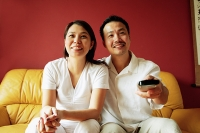 Couple sitting on sofa, watching TV, man holding TV remote control - Asia Images Group