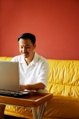 Man sitting on sofa, using laptop - Asia Images Group