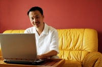 Man sitting on sofa, using laptop, looking at camera, portrait - Asia Images Group