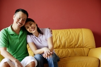 Couple sitting on sofa, side by side, looking at camera - Asia Images Group
