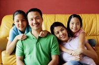 Family of four smiling at camera, portrait - Asia Images Group