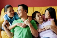 Family of four smiling at each other - Asia Images Group