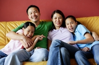 Family of four sitting on sofa, family portrait - Asia Images Group