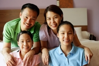 Family of four looking at camera, family portrait - Asia Images Group