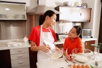 Two sisters baking in kitchen - Asia Images Group