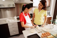 Mother and daughter in kitchen - Asia Images Group