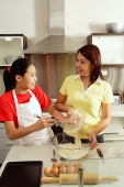 Mother and daughter in kitchen, preparing ingredients for baking - Asia Images Group