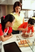 Mother and two daughters in kitchen, one daughter holding spoon and bowl - Asia Images Group