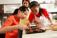 Mother and two daughters in kitchen, baking - Asia Images Group