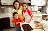 Mother and two daughters in kitchen, looking at camera - Asia Images Group