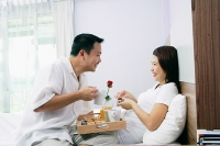 Couple in bedroom, breakfast tray between them - Asia Images Group