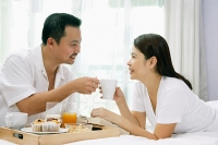 Couple in bedroom, having breakfast on bed - Asia Images Group