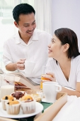 Couple on bed, with drinks, looking at each other, breakfast tray in front of them - Asia Images Group