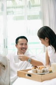 Couple in bedroom, breakfast tray on bed - Asia Images Group