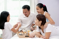 Family of four in bedroom, breakfast tray on the bed next to them - Asia Images Group