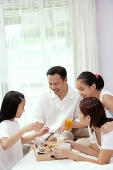 Family of four in bedroom, having breakfast in bed - Asia Images Group