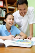 Girl doing homework, father standing next to her - Asia Images Group