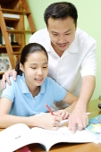 Girl doing homework, father standing next to her, pointing at book - Asia Images Group