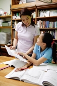 Girl showing mother homework - Asia Images Group