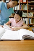 Girl doing homework, sister standing next to her - Asia Images Group