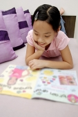 Girl reading magazine, lying on front - Asia Images Group