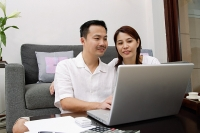 Couple in living room, using laptop - Asia Images Group