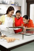 Mother and two daughters in kitchen, looking at tray of cookies - Asia Images Group