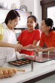 Mother and two daughters in kitchen, with tray of cookies - Asia Images Group