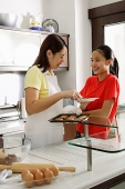 Mother and daughter in kitchen, mother holding tray of cookies - Asia Images Group