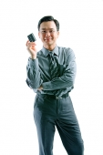 Businessman holding credit card, arms crossed, looking at camera - Asia Images Group