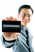 Businessman holding credit card - Asia Images Group