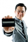 Businessman holding credit card, looking at camera - Asia Images Group